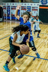 Girls playing basketball on indoor court at Artistic Stitch Sports Complex Queens, New York.